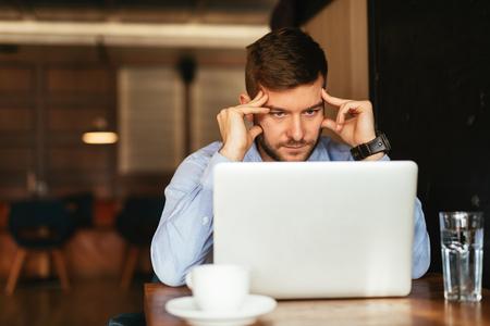 agotado: Hombre cansado que trabaja en la computadora portátil en un café. enfoque suave en las manos.
