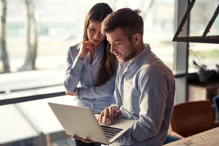 hombres trabajando: Dos colegas que buscan en un ordenador y en discusiones de negocios.