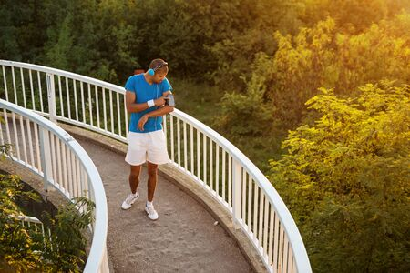 playlist: Shot of an attractive and sporty young man starting his music playlist.