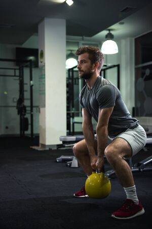 squats: Man doing squats with kettlebell in gym. Stock Photo