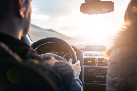 Traveling together towards the sun by car. Lens flare.