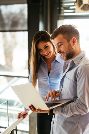 Two colleagues discussing work on a laptop. Stock Photo