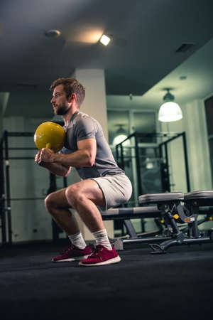 Man doing squats with kettlebell in gym.