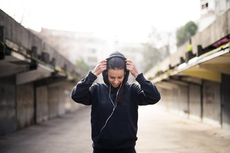 personas escuchando: atleta femenina que pone la capucha sobre.