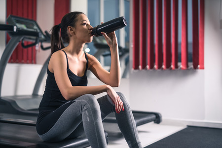 A beautiful young woman sitting at the gym and drinking water.