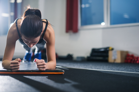 Female athlete doing exercises in a gym. Soft focus.
