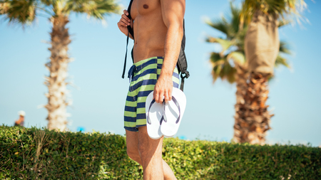 carrying: Man carrying slippers and going to the beach. Stock Photo