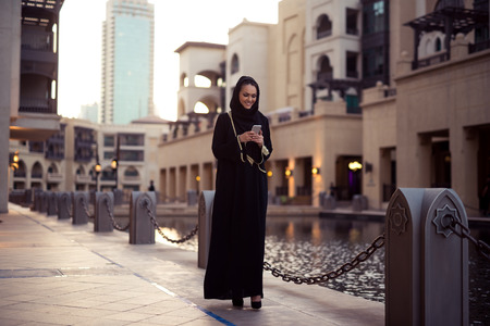 Muslim woman messaging on her mobile phone.