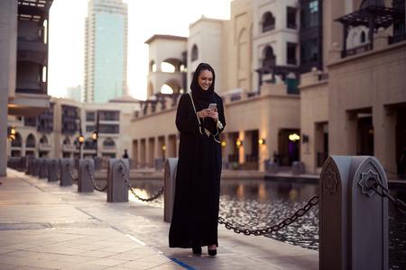 Moslimvrouw berichten op haar mobiele telefoon. Stockfoto