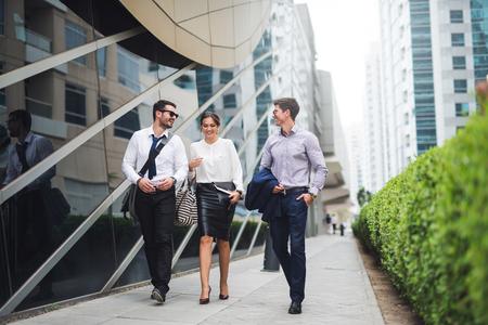 エレガントなビジネスマンは、近代的な都市で歩きます。