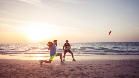 Man doing fitness on the beach with the help of personal trainer. Warm tone, lens flare. Archivio Fotografico