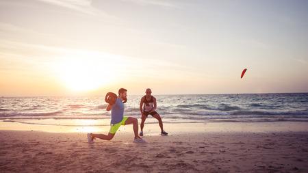 Man fitness op het strand met behulp van persoonlijke trainer. Warme toon, lensflare.