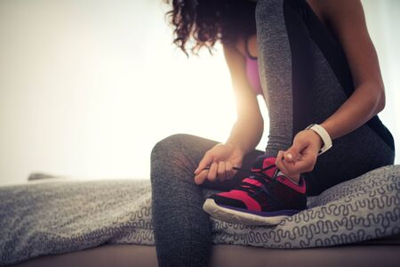 Woman tying a shoelace and preparing for fitness.