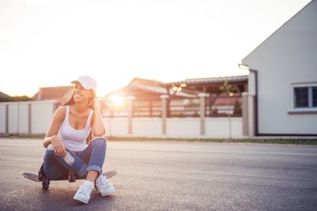 taking a break: Girl taking a break from skateboard.