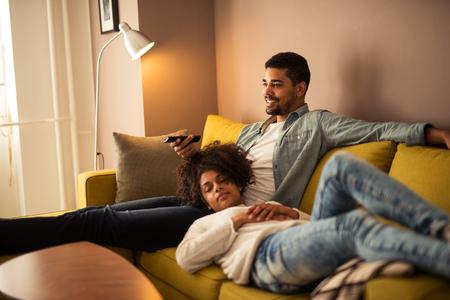 Man kijken naar een televisie, terwijl zijn vriendin slaapt. Stockfoto