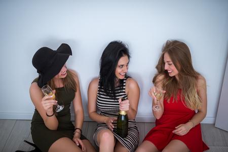 bebidas alcohÓlicas: chicas borrachos sentados en el suelo y bebiendo un vino.