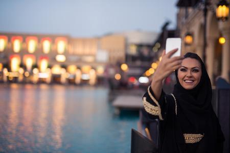 Cute muslim girl making a selfie while shopping.