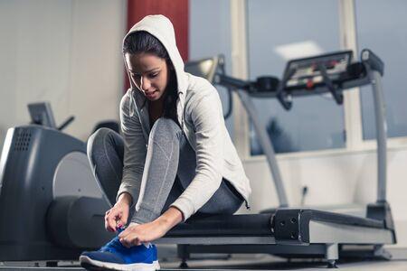 Sportswoman tying a shoelace on her sneakers.