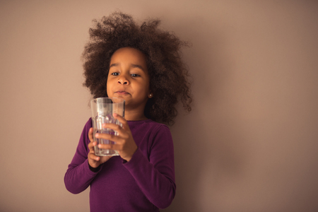 curly hair child: Cute african american girl drinking water.