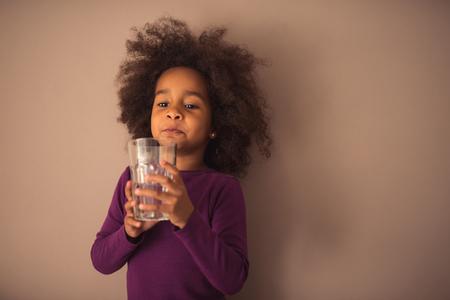 Cute african american girl drinking water.