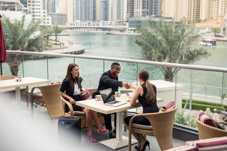 business woman working: Businesspeople having a meeting outdoors.