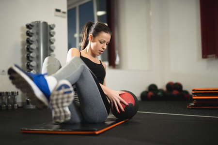 workouts: Woman doing exercise with ball in the gym. Stock Photo