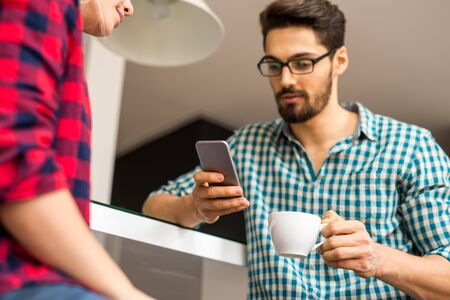 busy person: Couple enjoying coffee together and using mobile phones.