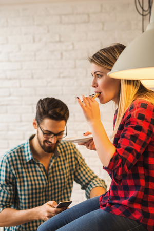 surfing the net: Woman eating a cookie while her boyfriend is surfing the net Stock Photo