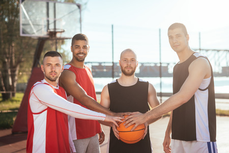 ouside: Team of basketball players holding a ball. Stock Photo