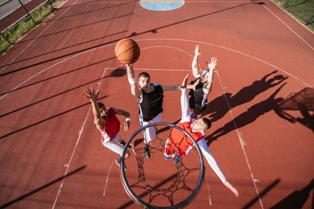 Team of basketball players playing basketball outdoors.