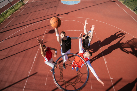 outdoor basketball court: Team of basketball players playing basketball outdoors.