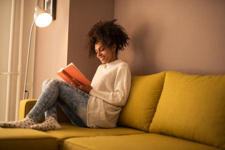 Joven mujer afroamericana de leer un libro en casa. Foto de archivo - 58281593
