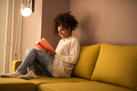 attractive couch: Young african american woman reading a book at home.