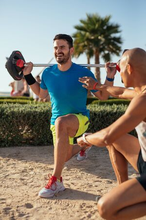 asian bodybuilder: Man doing fitness on the beach with the help of personal trainer. Stock Photo