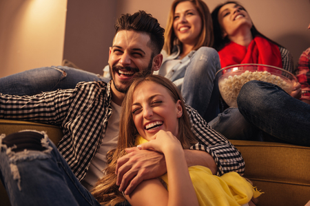 party room: Group of friends enjoying movie time at home.