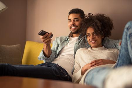 personas viendo television: Recortar foto de una joven pareja afroamericana viendo la televisión en casa
