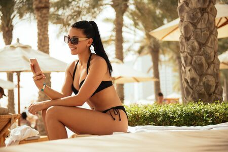 mobile sms: Attractive woman using mobile phone on a summer holiday. Stock Photo