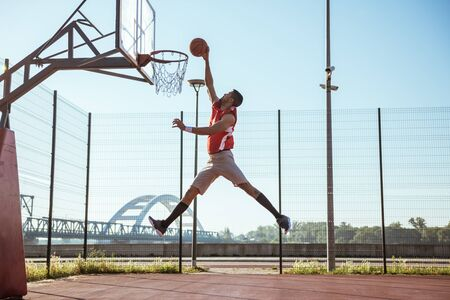 dunk: A young basketball player scoring a slam dunk. Stock Photo