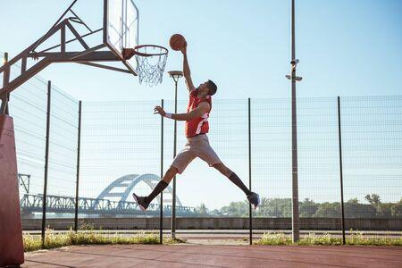 Un jeune joueur de basket-ball de marquer un slam dunk.