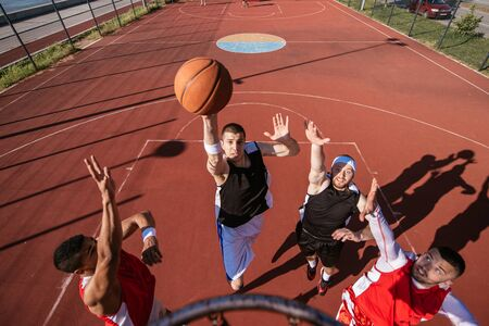 ouside: A young basketball player scoring a slam dunk. Stock Photo
