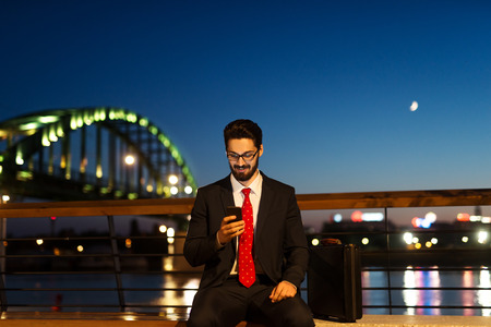 busy person: Handsome businessman working outdoors late at night.