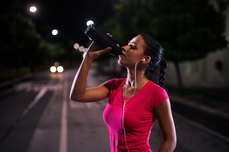 active listening: Young girl having a refreshment after a night running session. High ISO