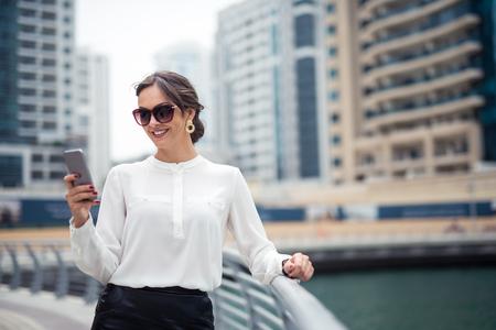mujeres elegantes: Elegante empresaria mensajes de texto en un teléfono móvil al aire libre.