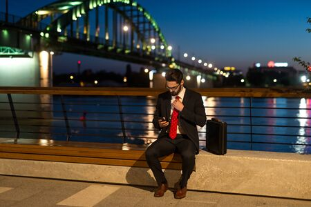 working overtime: Handsome elegant businessman working overtime at night in the city.