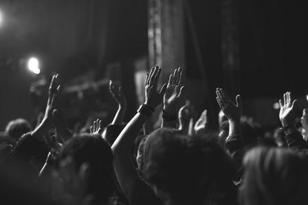 Zwart-wit foto van de menigte het verhogen van hun handen op een festival. Stockfoto