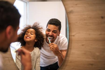 Chica afroamericana cepillarse los dientes con el papá.