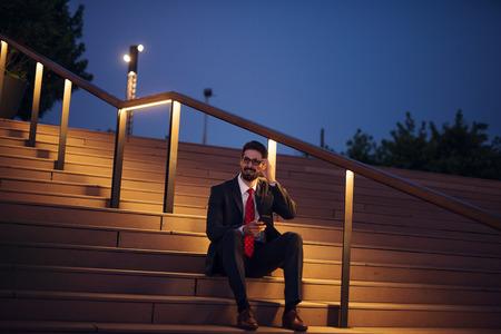 working overtime: Elegant businessman working overtime outdoors.