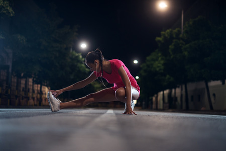 Young girl doing fitness outdoors at night. Banque d'images