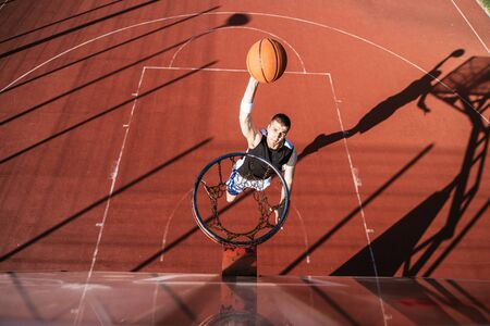ouside: Basketball player scoring a slum dunk. Stock Photo
