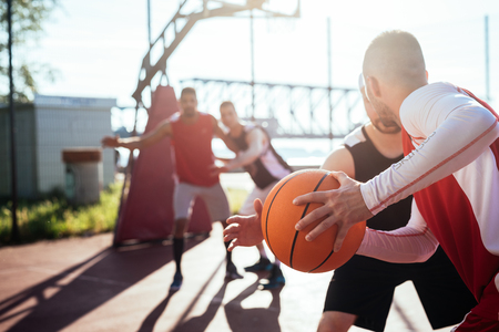 outdoor basketball court: Man passing the ball to another player. Stock Photo